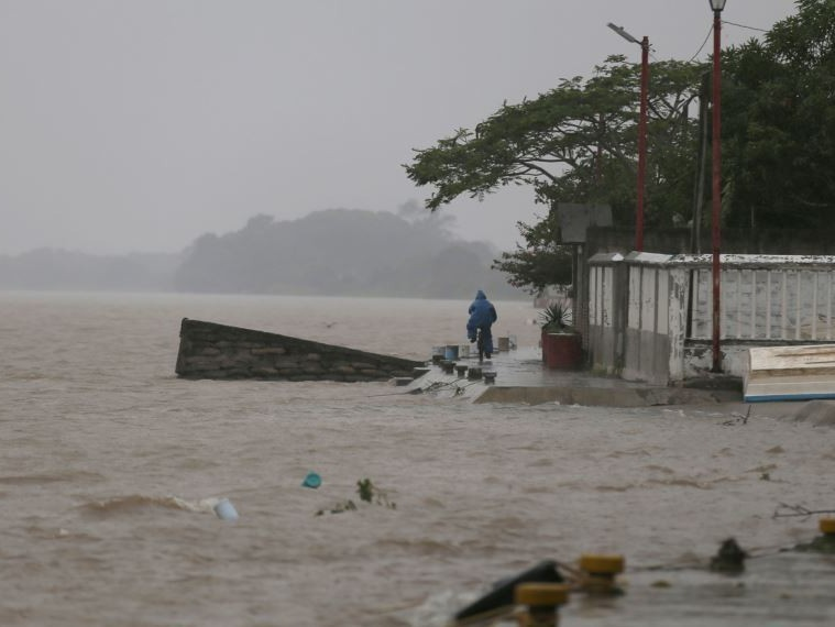 A man rides his bicycle next to Tecolutla river before the arrival of Hurricane Katia, in Tecolutla, Veracruz state, Mexico, Friday, Sept. 8, 2017.  Hurricane Katia in the Gulf of Mexico is stationary about 190 miles (310 kilometers) north-northeast of Veracruz and forecasters didn't expect much movement overnight. (AP Photo/Eduardo Verdugo)
