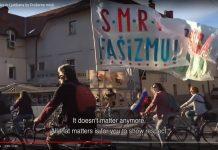 """Словенечки демонстранти на велосипеди меѓу кои и човек кој носи знамиња на кои пишува """"Смрт на фашизмот"""" и """"Слобода на народот"""". Фото: снимка од екранот од видеото од Бајк Штрајк на Јутјуб."""